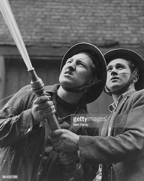 Eighteen yearolds Graham Bath and Jackie Duggan fight a fire caused by an air raid London April 1941 They are members of the 'Dead End Kids' a gang...