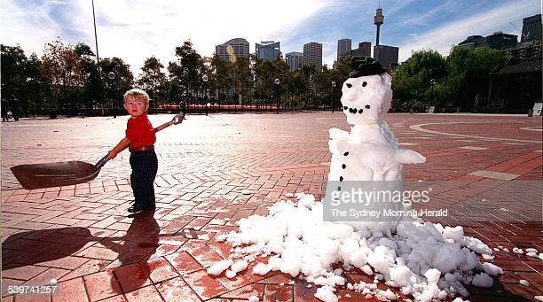 Eighteenmonthold Patrick Killen of Cooma plays with a shovel near a melting snowman on an unseasonally hot Sydney day with tremperatures nearing 26...