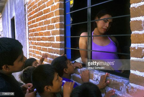 Eighteenyearold Raul wearing an evening dress receives attention from kids on the street in Juchitan Mexico October 16 2002 Queen America was chosen...