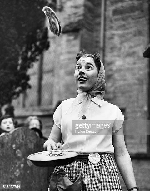 Eighteenyearold Sandra Sibley the winner of a pancake race tosses a pancake at the race's end in Olney England