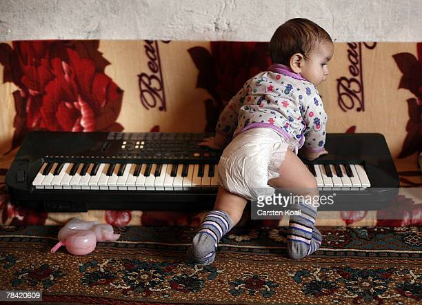 Eightmonthold Roma refugee Sabit plays on a keyboard in her family's house in the Cesmin Lug refugee camp in the Serbian district December 12 2007 in...