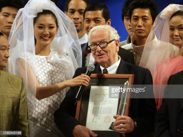 Eighty four-year-old French icon Pierre Cardin with an award from China Fashion Association as he is surrounded by his Chinese models, as he presents...