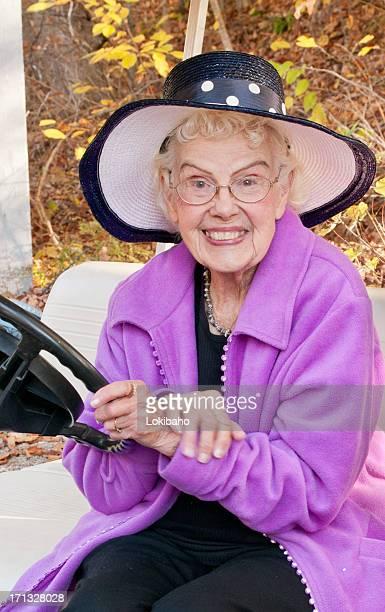 Eighty year old woman behind steering golf cart