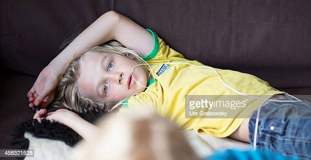 Eightyearold boy is listening to an audiobook with headphones on a couch on August 05 in Sankt Augustin Germany Photo by Ute Grabowsky/Photothek via...