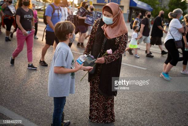 """Eight-year-old Danny gives a rose to a Muslim woman as members of the Muslim community and supporters gather for a multi-faith """"March to End Hatred""""..."""