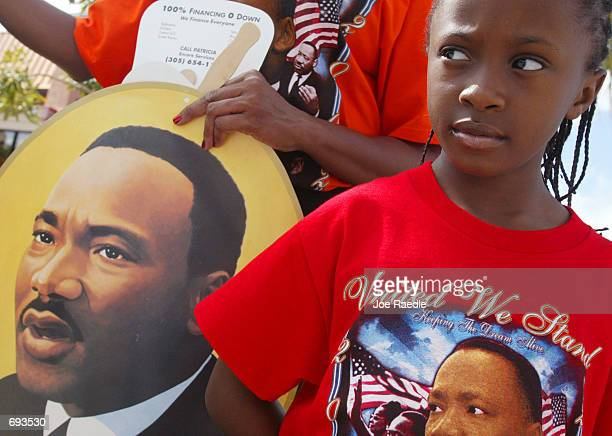 Eightyearold LaKedia Logana watches the Liberty City Parade in honor of slain civil rights leader Martin Luther King Jr January 21 2002 in Miami...