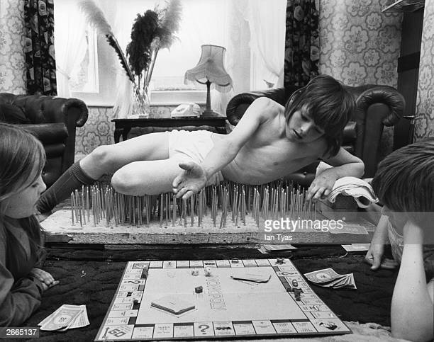 Eight-year-old Mark Harman from London enjoying a game of Monopoly with his brother Graham and sister Belinda, from his bed of nails. Mark is being...