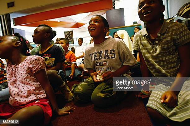 Eight-year-old Marshal Gordon , watches circus clowns at a free performance at the Dallas Public Library on June 17, 2009 in Dallas, Texas. Dozens of...