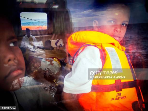 TOPSHOT Eightyearold Samir from Somalia looks out of the window of the Astral rescue ship from the nongovernmental organisation Proactiva Open Arms...