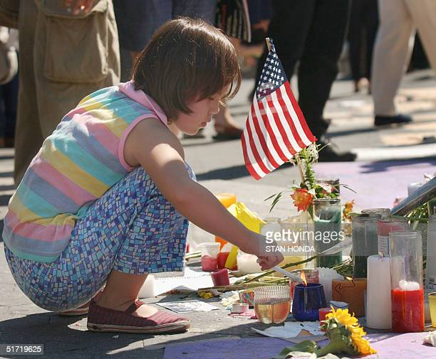 Eightyearold Shirley Wetherhold lights a candle at a public memorial in Union Square in New York 13 September 2001 dedicated to the victims of the...