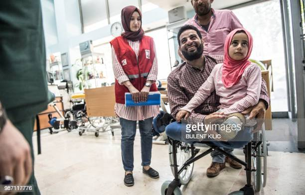 TOPSHOT Eightyearold Syrian girl Maya and her father born without legs arrive to an Istanbul clinic on June 29 to get prosthetic legs after being...