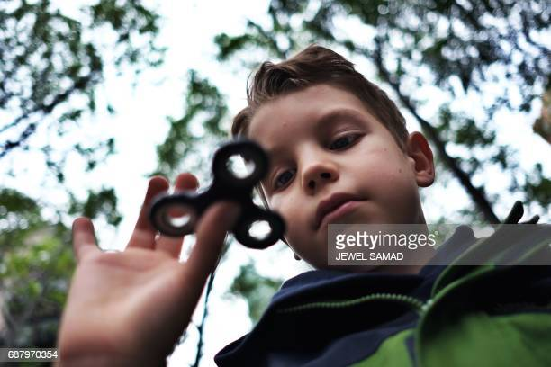 Eightyearold Tom Wuestenberg plays with a fidget spinner in a park in New York on May 23 2017 It was supposed to calm nerves relieve stress and...