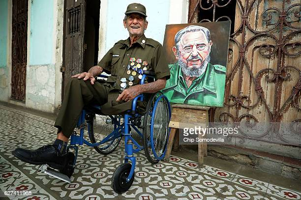Eightysevenyearold Don Altilo Boijoli a personal chauffer to former Cuban President Fidel Castro during the early 1960s poses next to a portrait of...
