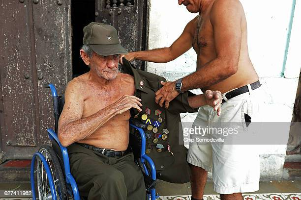 Eightysevenyearold Don Altilo Boijoli a personal chauffer to former Cuban leader Fidel Castro during the early 1960s gets help from his son to put on...