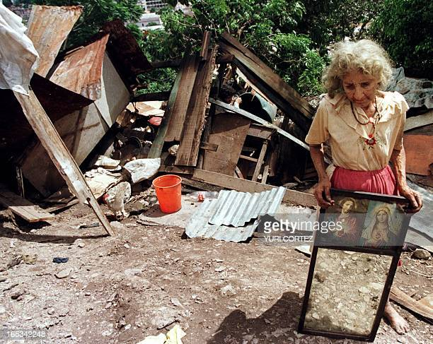 Eightyyearold Irene Avila rescues a mirror with portraits of Jesus Christ and the Virgin Mary outside her destroyed dwelling 01 November in...