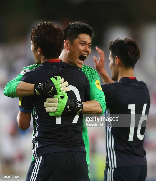 Eiji Kawashima of Japan celebrates victory with Hiroki Sakai and Hotaru Yamaguchi of Japan after the FIFA 2018 World Cup qualifying match between...