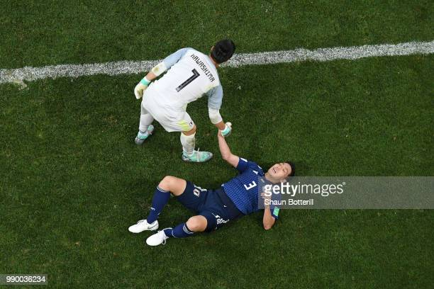 Eiji Kawashima of Japan consoles Gen Shoji of Japan following the 2018 FIFA World Cup Russia Round of 16 match between Belgium and Japan at Rostov...
