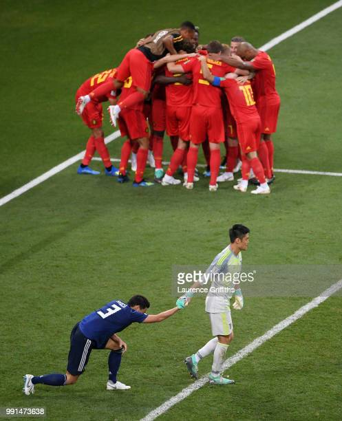 Eiji Kawashima of Japan helps his team mate Gen Shoji to his feet as Nacer Chadli of Belgium is congratulated on scoring the winning goal during the...