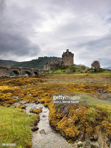 CONTENT] Eilean Donan Castle on Loch Duich on stormy day a river flows into the lake clean waters through piles of orange algae Scotland