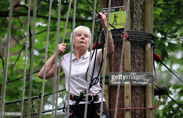 Eileen Noble navigates treetop crossing as she becomes the oldest person to complete the Go Ape Treetop Challenge at Leeds Castle, Maidstone in Kent.