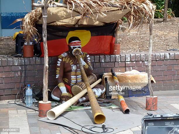 Ein Aboriginal musiziert auf dem traditionellen Blasinstrument Didgeridoo Im Hintergrund die Flagge der Ureinwohner