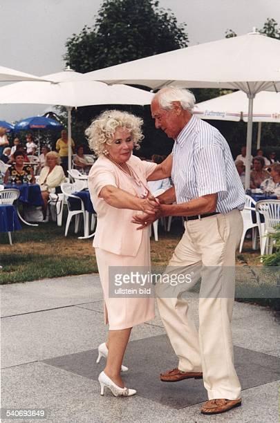 Ein alter Herr mit seiner Tanzpartnerin auf der Tanzfläche eines Gartencafés