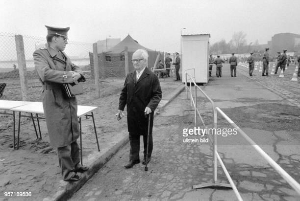 Ein alter Mann aus BerlinWest kommt über den provisorisch enigerichteten Grenzübergang am Potsdamer Platz zu einem DDRGrenzer der mit einem...