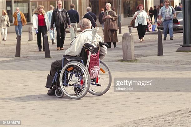 Ein alter Mensch fährt im Rollstuhl eine Einkaufsstraße entlang Hinter der Rückenlehne sind Gehhilfen befestigt Im Hintergrund vorbeieilende...