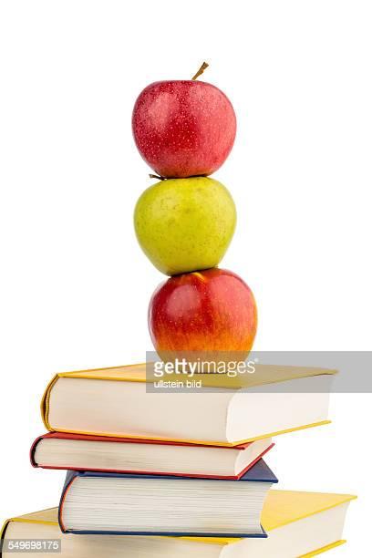 Ein Apfel liegt auf einem Bücherstapel. Symbolfoto für gesunde und vitaminreiche Nahrung in der Schulpause.