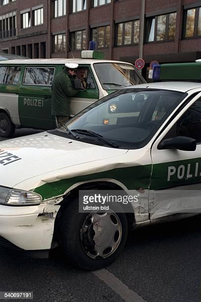 Ein Auto der Polizei ist nach einem Verkehrsunfall im Bereich des linken Kotflügels zerbeult und verschrammt Im Hintergrund ein Polizeibulli...