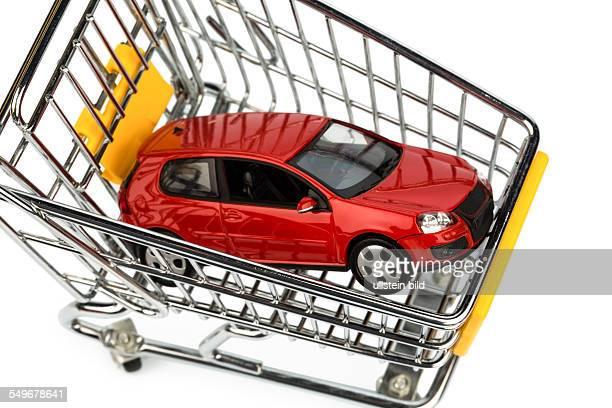 Ein Auto im Einkaufswagen als Symbol für Autokauf und Leasing