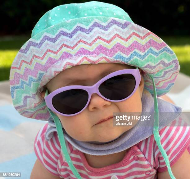 Ein Baby mit Sonnenbrille und Sonnenhut ist gut gegen die Hitze im Sommer ausgestattet