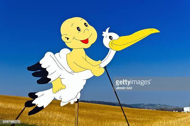 Ein Baby sitzt auf einem Storch Symbolfoto für Geburtenrate