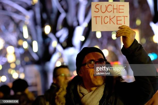 Ein Besucher der 66 Internationalen Filmfestspiele Berlin sucht mit einem Hinweisschild vor dem Berlinale Palast nach einer Karte
