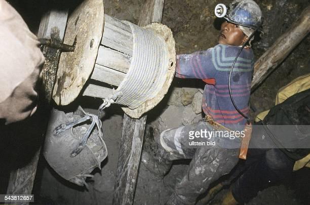 Ein bolivianischer Minenarbeiter bei der Arbeit in einer Silbermine des Cerro Rico bei Potosi Der Mineiro zieht an einer Winde aus Holz einen...