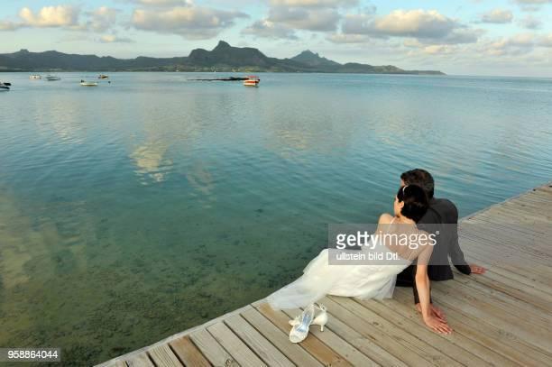 Ein Brautpaar am Strand blickt auf das Meer, Preskil Beach Resort von Mauritius