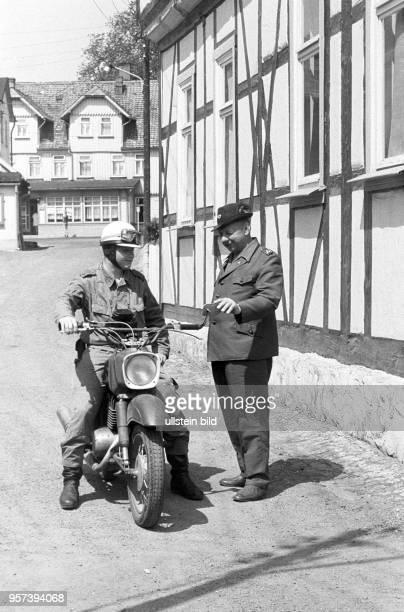 Ein DDRGrenzer der NVA auf einem Motorrad unterhält sich mit einem Förster im DDRGrenzort Schierke imHarz aufgenommen im Juli 1976 Die innerdeutsche...