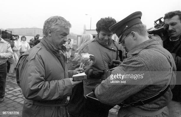 Ein DDRGrenzer kontrolliert an dem provisorisch eingerichteten Grenzübergang am Potsdamer Platz die Dokumente eines Mannes und stellt mit seinem...