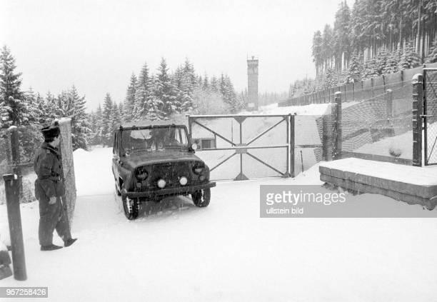 Ein DDRGrenzsoldat einer NVAGrenzkompanie bei Schierke am Brocken im Harz öffnet ein Metalltor zur Durchfahrt eines Geländewagens im Grenzgebiet der...