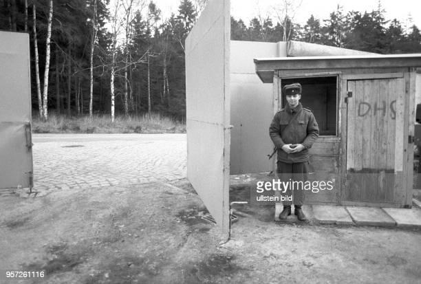 Ein DDRGrenzsoldat mit umgehängter Maschinenpistole steht Wache am Eingang zur Kaserne der Grenzkompanie Schierke am Brocken aufgenommen im Februar...
