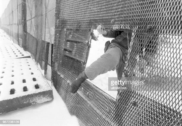 Ein DDRGrenzsoldaten einer NVAGrenzkompanie bei Schierke am Brocken im Harz steigt durch eine Öffnung im Metallgitterzaun der Grenzanlagen am Brocken...
