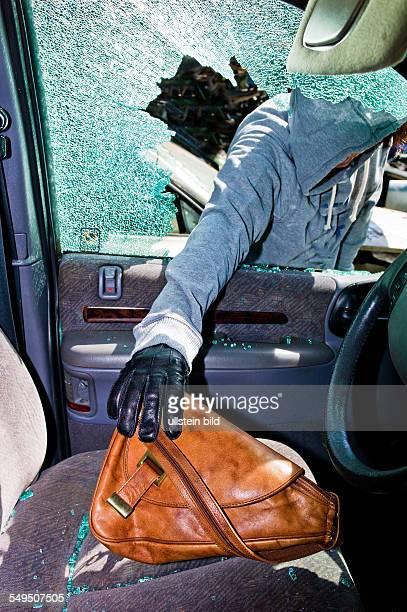 Ein Dieb entwendet eine Handtasche aus einem Auto durch eine zerbrochene Seitenscheibe.