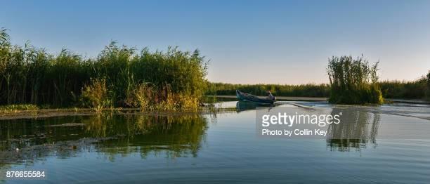 Ein einzelner Fischer steuert sein Boot duch das Delta der Donau