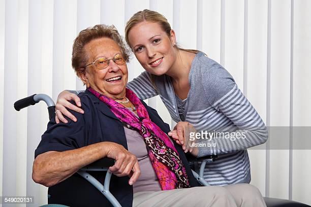 Ein Enkelin besucht seine Großmutter die im Rollstuhl sitzt