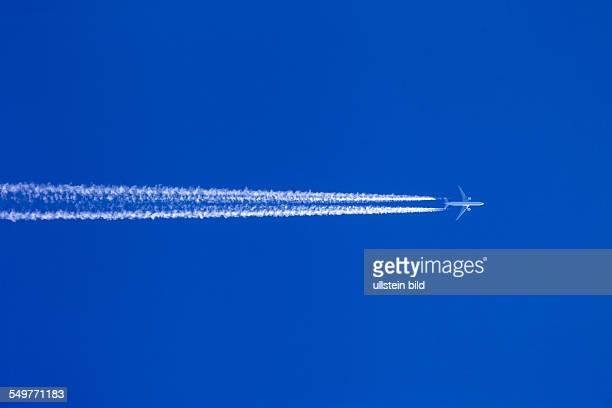 Ein Flugzeug mit Kondensstreifen vor blauem Himmel Urlaubsreise und Luftverschmutzung