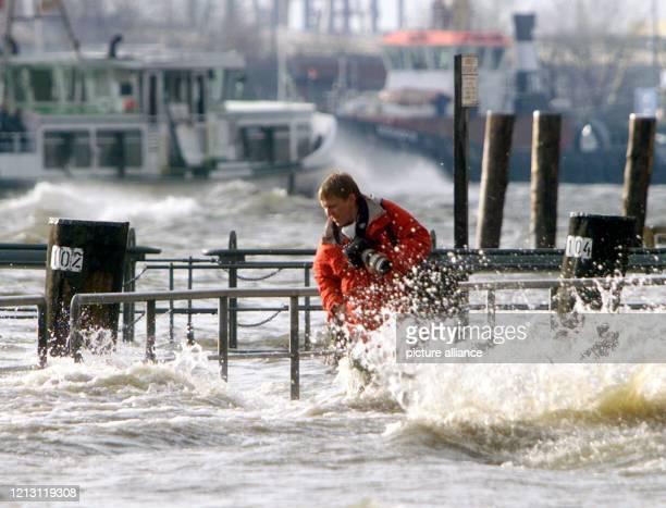 Ein Fotograf bahnt sich am 4121999 auf der Suche nach einem Motiv einen Weg durch das Hochwasser am überfluteten Hamburger Fischmarkt Eines der...