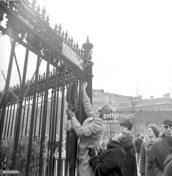 Ein Frau befestigt eine Rose am frisch enthüllten neuen Straßennamen Place CharlesdeGaulle aufgenommen am in Paris Der Platz wurde zu Ehren des kurz...
