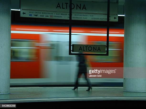Ein Frau steht am Bahnsteig des Bahnhofes Altona. Im Hintergrund ein einfahrender Zug der S-Bahn. Im Vordergrund ein Stationsschild mit der...