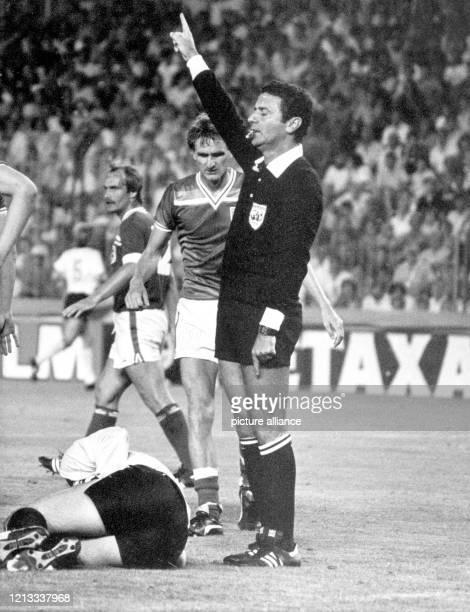 Ein gefoulter deutscher Spieler liegt zusammengekrümmt verletzt am Boden, der brasilianische Schiedsrichter Arnaldo C. Coelho entscheidet mit...