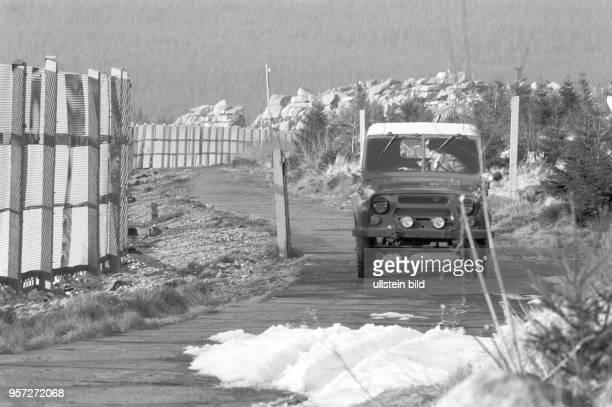 Ein Geländewagen der NVAGrenztruppen bei der Kontrollfahrt auf dem Kolonnenweg neben dem Metallgitterzaun der DDRGrenzanlagen im Harz bei...